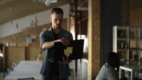 De aantrekkelijke geconcentreerde jonge bedrijfsmens loopt met zwarte laptop in zijn hand en het typen Kaukasische mens die binne stock video