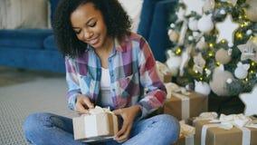De aantrekkelijke gemengde doos van de de verpakkingsgift van het rasmeisje dichtbij Kerstboom thuis stock afbeelding