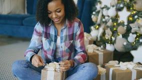 De aantrekkelijke gemengde doos van de de verpakkingsgift van het rasmeisje dichtbij Kerstboom thuis Stock Foto