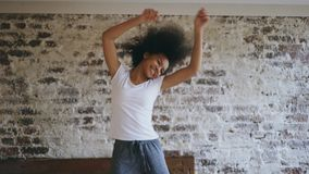 De aantrekkelijke gemengde ras jonge blije vrouw heeft pret thuis dansend dichtbij bed Royalty-vrije Stock Foto