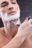 De aantrekkelijke geschikte kerel scheert zijn baard stock foto