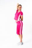 De aantrekkelijke geschikte vrouw in roze sportsuit warmt op Stock Fotografie