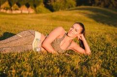 De aantrekkelijke geschiktheidsvrouw in sportkleding ligt op het gras in Stock Foto's