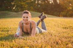 De aantrekkelijke geschiktheidsvrouw in sportkleding ligt op het gras in Royalty-vrije Stock Foto's