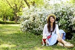 De aantrekkelijke hipster jonge vrouw ging voor een gang die in het park, met leuk de terriërpuppy van hefboomrussell spelen op d Royalty-vrije Stock Fotografie