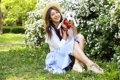 De aantrekkelijke hipster jonge vrouw ging voor een gang die in het park, met leuk de terriërpuppy van hefboomrussell spelen op d Stock Foto