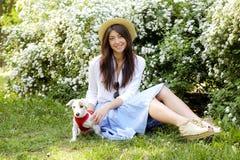 De aantrekkelijke hipster jonge vrouw ging voor een gang die in het park, met leuk de terriërpuppy van hefboomrussell spelen op d Stock Fotografie