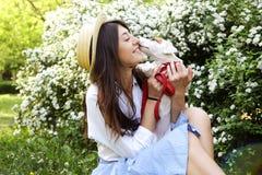 De aantrekkelijke hipster jonge vrouw ging voor een gang die in het park, met leuk de terriërpuppy van hefboomrussell spelen op d Royalty-vrije Stock Foto