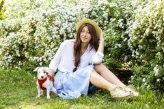De aantrekkelijke hipster jonge vrouw ging voor een gang die in het park, met leuk de terriërpuppy van hefboomrussell spelen op d Stock Foto's