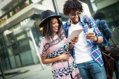 De aantrekkelijke jonge Afrikaanse studenten gebruiken een digitale tablet en glimlachen terwijl buiten status stock fotografie