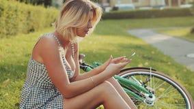 De aantrekkelijke jonge blondevrouw in een modieuze witte kleding zit op het gazon in het stadspark door de groene wijnoogst stock footage