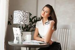 De aantrekkelijke jonge bussinesswoman dragende klassieke kleren en het houden van glazen zitten thuis in haar kabinet en voorber Royalty-vrije Stock Foto's