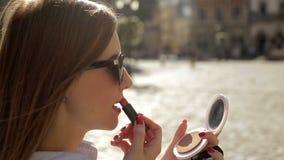 De aantrekkelijke jonge dame terwijl het kijken op de spiegel maakt haar lippen door een nieuwe glamourlippenstift op de straat r stock video