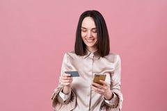 De aantrekkelijke jonge donkerbruine vrouw in een modieuze blouse maakt online aankopen en gebruikt een telefoon en een Betaalpas royalty-vrije stock fotografie