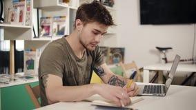 De aantrekkelijke jonge mannelijke programmeursleraar schrijft iets die in zijn notitieboekje neer, zeer ernstig kijken stock video