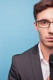De aantrekkelijke jonge mannelijke verslaggever werkt met Stock Foto's
