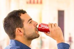 De aantrekkelijke jonge mens die Coca-Cola drinken kan Stock Foto