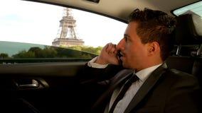 De aantrekkelijke jonge mens in een kostuum zit in de auto naast de Toren van Eiffel stock video
