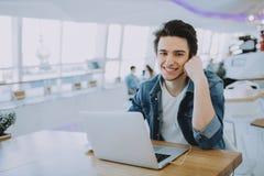 De aantrekkelijke jonge mens of freelance zit in koffie en gebruikt zijn mobiel royalty-vrije stock foto