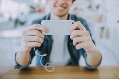 De aantrekkelijke jonge mens of freelance zit in koffie en gebruikt zijn mobiel royalty-vrije stock foto's