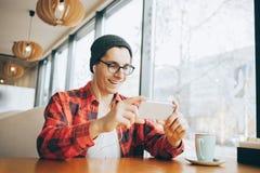 De aantrekkelijke jonge mens of freelancer zit in koffie en het letten op video stock afbeelding