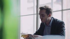 De aantrekkelijke jonge mens zit alleen in de bar, gebruikt zijn telefoon, neemt foto, brandingen Internet, een slokje van het bi stock video