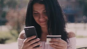 De aantrekkelijke jonge mobiele telefoon die van het vrouwengebruik online en betaalt met Internet-bankwezen openlucht bij hete d stock footage