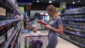 De aantrekkelijke jonge moeder kiest een fles wijn in drankenafdeling in de supermarkt, terwijl haar weinig baby stock footage
