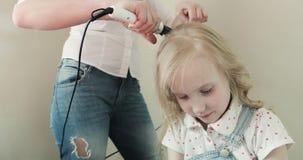 De aantrekkelijke jonge moeder maakt een klein meisje tot een kapsel stock videobeelden