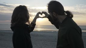 De aantrekkelijke jonge paarzitting op het strand die op de zonsondergang letten en een hartvorm met hun maken dient langzame mot stock videobeelden