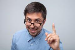 De aantrekkelijke jonge slimme mens heeft een joviaal idee stock foto's