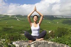 De aantrekkelijke jonge vrouw die een yoga doen stelt voor saldo Royalty-vrije Stock Foto