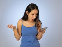 De aantrekkelijke jonge vrouw die mobiele geschokt en verraste smartphone bekijken verloren hebben van houdt van stock fotografie