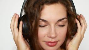 De aantrekkelijke jonge vrouw draagt hoofdtelefoons luisterend aan muziek op de muziekspeler stock video