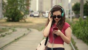 De aantrekkelijke jonge vrouw draagt hoofdtelefoons luisterend aan muziek op de muziekspeler stock videobeelden