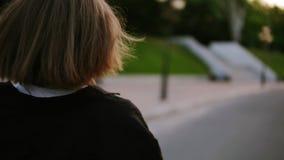 De aantrekkelijke jonge vrouw in een modieuze uitrustingsdraaien aan camera en glimlacht seductively, blijft lopend vanaf stock video