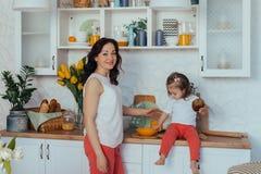 De aantrekkelijke jonge vrouw en haar weinig leuke dochter koken op keuken royalty-vrije stock afbeelding