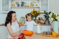 De aantrekkelijke jonge vrouw en haar weinig leuke dochter koken op keuken royalty-vrije stock foto