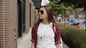 De aantrekkelijke jonge vrouw kiest de muziek op haar smartphone in de stad stock footage