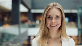 De aantrekkelijke jonge vrouw kijkt de camera van AR glimlachend voelt gelukkig in de kledingsmeisje van de wandelgalerij het dic stock video