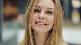De aantrekkelijke jonge vrouw kijkt de camera van AR glimlachend voelt gelukkig in de kledingsmeisje van de wandelgalerij het dic stock videobeelden