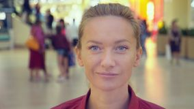 De aantrekkelijke jonge vrouw kijkt de camera van AR glimlachend voelt gelukkig in wandelgalerij Sluit omhoog Shopaholic 4K stock footage