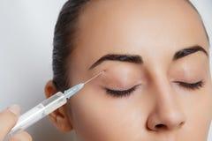 De aantrekkelijke jonge vrouw krijgt kosmetische injectie Stock Afbeeldingen