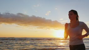 De aantrekkelijke jonge vrouw loopt langs de kust bij zonsondergang Neem in sporten in dienst - gezonde levensstijl Langzame Stea stock footage