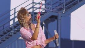 De aantrekkelijke jonge vrouw maakt zeepbels op straat, langzame motie 120 fps stock videobeelden