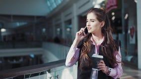 De aantrekkelijke jonge vrouw met mooie samenstelling in het roze overhemd loopt in het winkelcentrum met een kop van koffie stock video