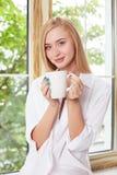 De aantrekkelijke jonge vrouw ontspant dichtbij een venster Royalty-vrije Stock Fotografie