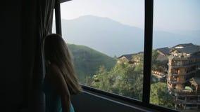 De aantrekkelijke Jonge Vrouw opent Gordijnen stock videobeelden