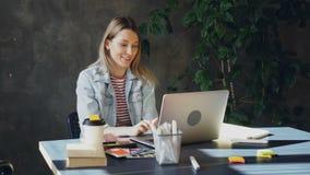 De aantrekkelijke jonge vrouw spreekt op skype op laptop terwijl het zitten bij lijst in modern bureau Zij spreekt