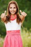 De aantrekkelijke jonge vrouw toont duimen Stock Fotografie